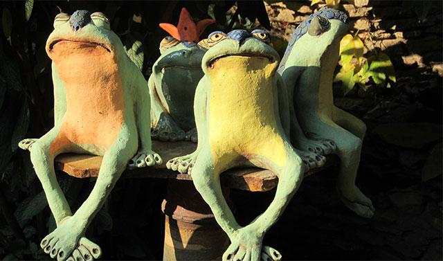 Hosszú lábú kerámia békák üldögélnek egy oszlop tetején az őszi napsütésben