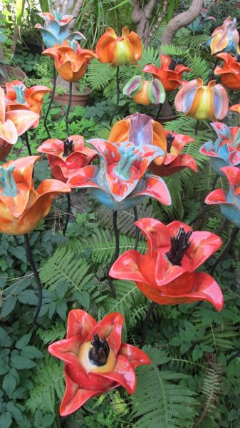 Kerti kerámia virágok élénk színekben kovácsoltvas szárral.