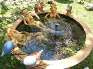Kerámia szobrok medencében üldögélnek.