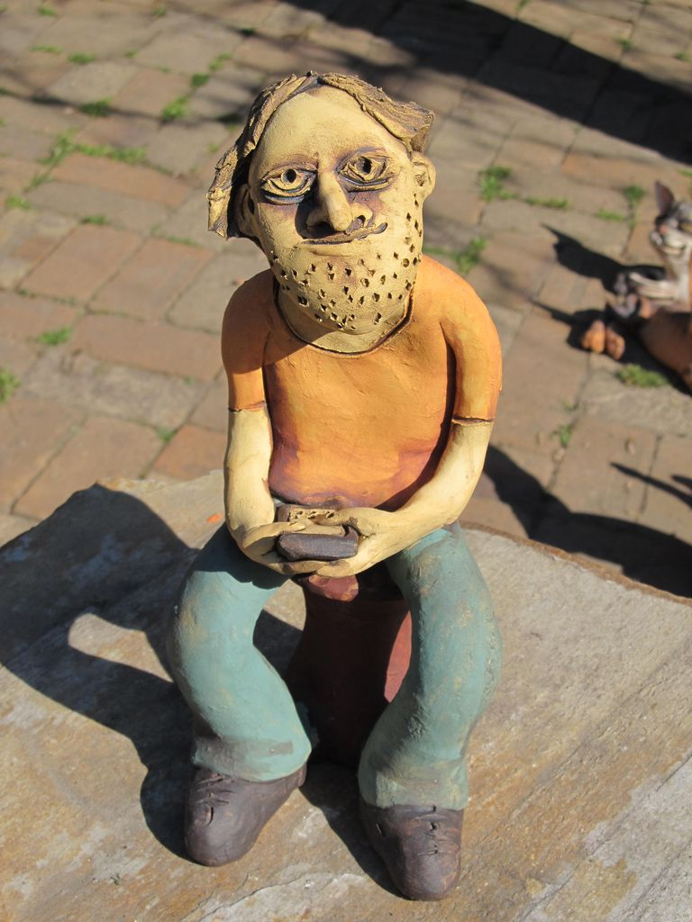 Kerámia figura, a kezében telefont tartó fiú.
