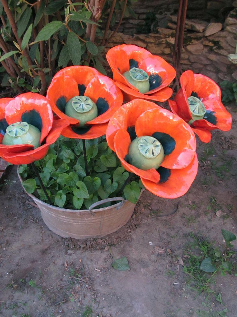 Vas szárú, pipacs formájú kerámia virágok élénk piros színben, egy cserépbe szúrva.