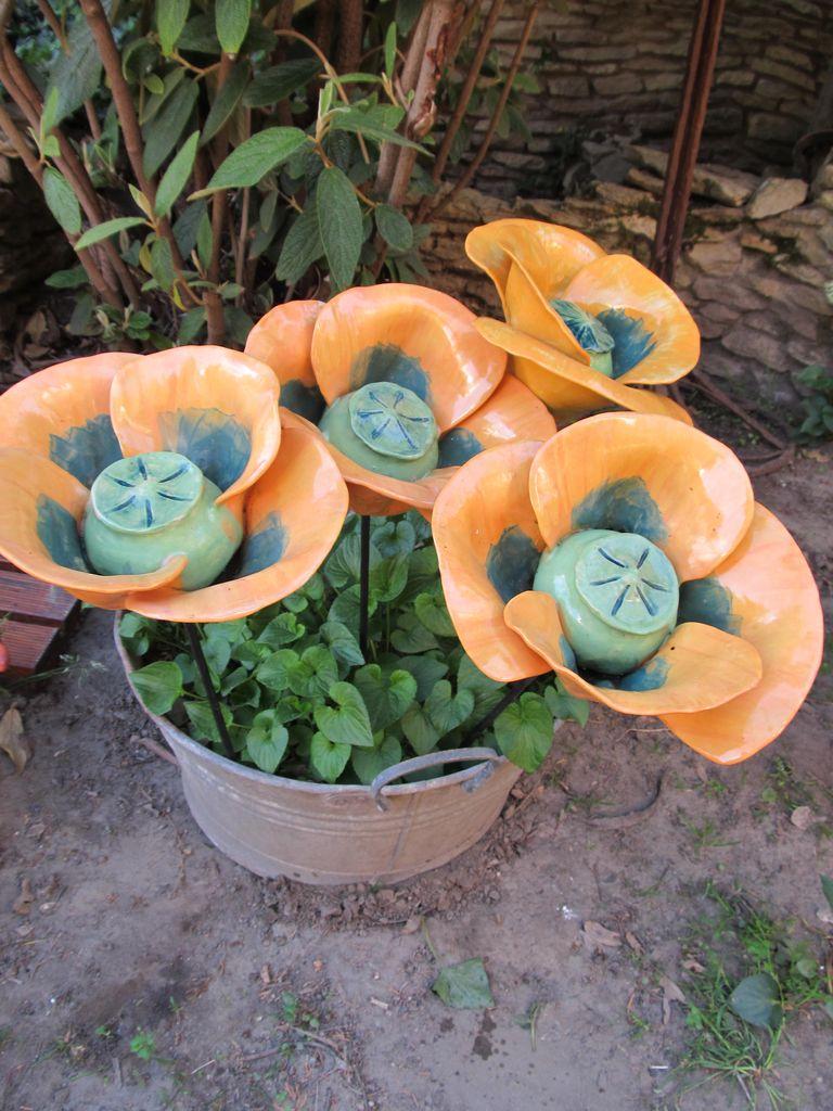 Vas szárú, pipacs formájú kerámia virágok sárga színben, egy cserépbe szúrva.