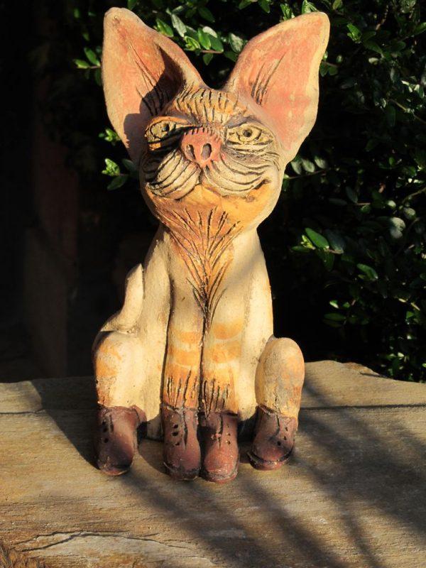Macska szobor, narancssárga csíkokkal és rózsaszín füllel, fűzős cipőben.