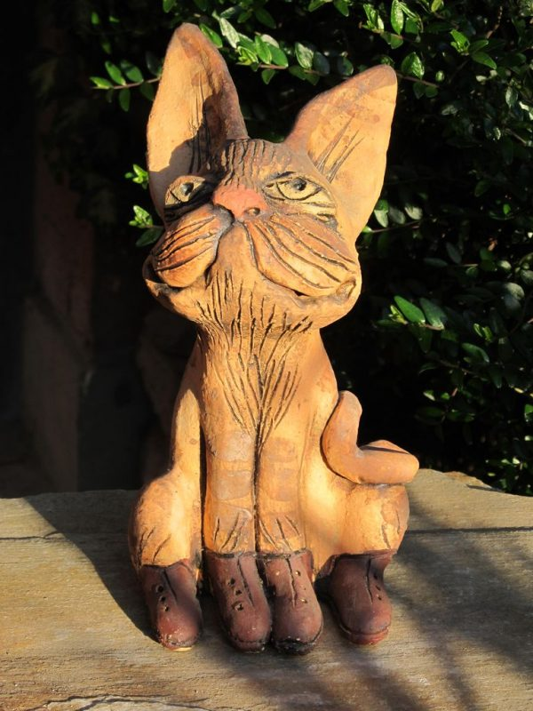 Macska szobor kerámiából, okker színben, fűzős cipőben.