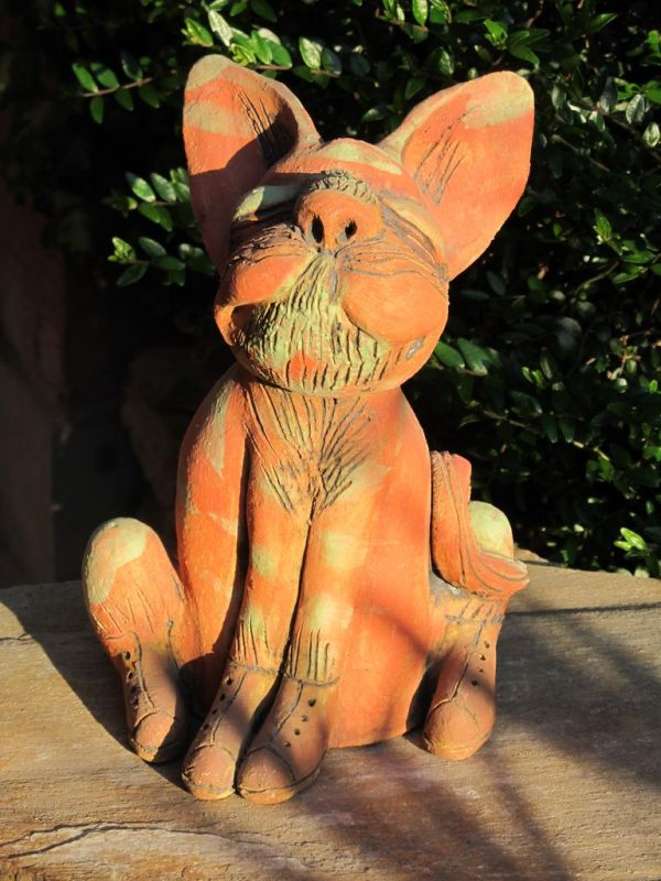 Macska szobor kerámiából, narancssárga és zöld csíkokkal, fűzős cipőben.