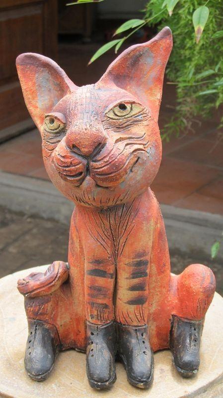 Macska szobor, narancssárga bundával és fűzős cipőben.