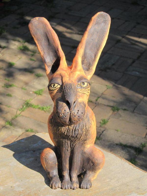 Ülő nyúl szobor kerámiából, barna és okker színben.