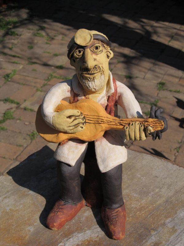 Kerámia figura, szakállas orvos gitárral a kezében, a fején gégész tükörrel.