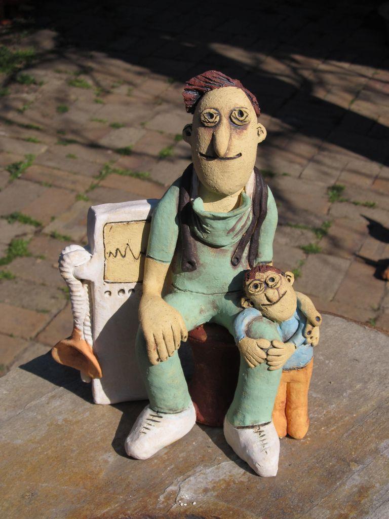 Kerámia figura, orvos műtős ruhában kisgyerekkel és lélegeztetőgéppel.