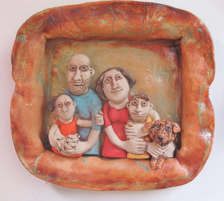 Kerámia falikép négytagú családdal és kutyával.
