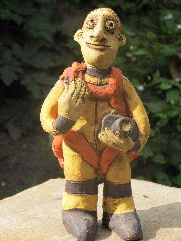Kerámia ejtőernyős figura sárga ugróruhában.
