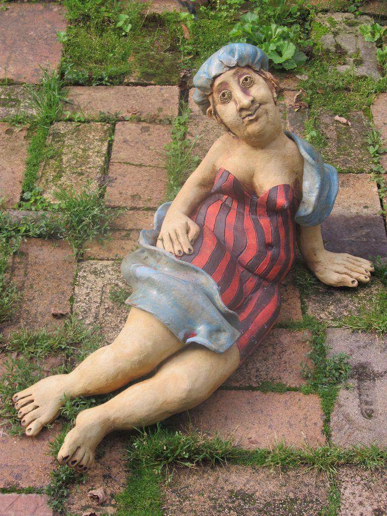 Kerámia szobor, napozó nőci csíkos fürdőruhában.