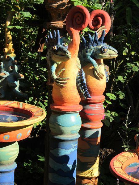 Kaméleon szobor kerámiából nagy oszlopon, élénk színekben.