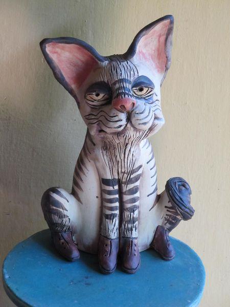 Macska szobor kerámiából, szürke csíkokkal, rózsaszín orral.