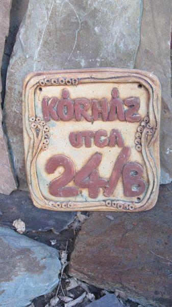 Kerámia házszám agyaghurkából gyúrt betűkkel.