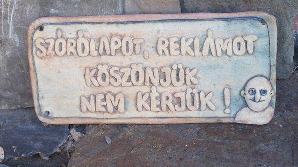 Kerámia tábla agyaghurkákból gyúrt betűkkel.