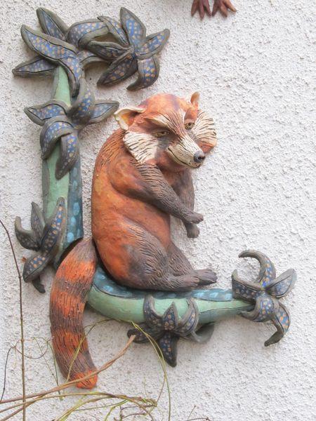 Kerámia fali dekoráció, ágon ülő macskamedve szobor.