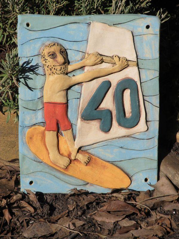 Kerámia házszám szörfös figurával.