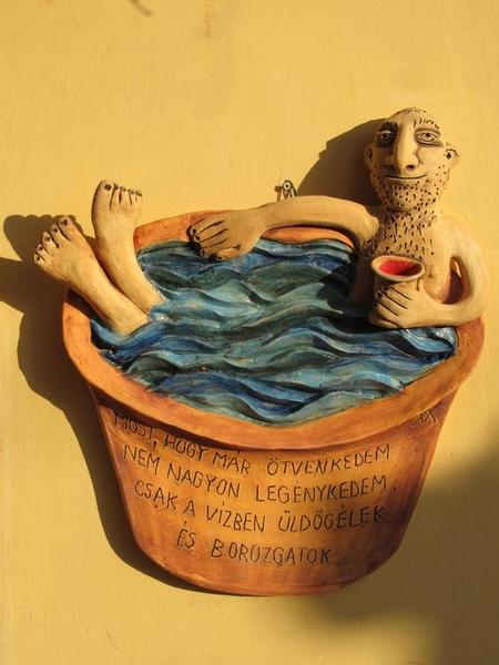 Kerámia falikép kádban borozgató figurával, ötvenedik születésnapra szánt versikével.