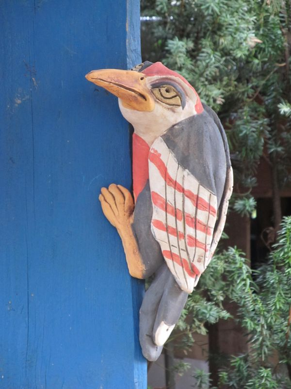Kerámia harkály szobor, fa kerítésen.